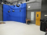 Part of a small television studio with blue curtain and hanging lights