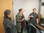 Three people in the studio's control room