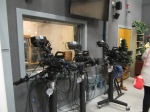 three studio camera on rolling stands with the control room window behind them