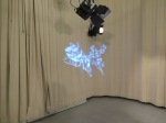 a light projection of Santa Claus, sleigh, and two reindeer on an off-white curtain of the studio