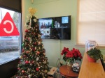 the building lobby, with a Christmas tree, poinsettia on a table, as well as a widescreen TV on the wall